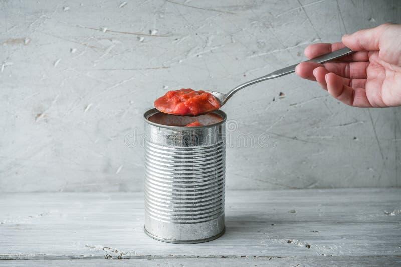 Mano femenina que sostiene una cuchara con los tomates asados fotos de archivo libres de regalías