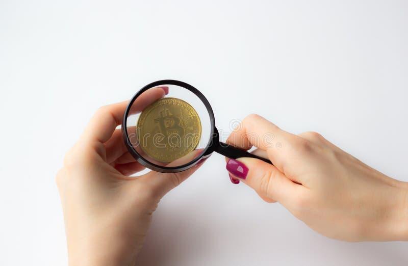 Mano femenina que sostiene una lupa con la moneda de oro del bitcoin en el fondo blanco fotografía de archivo libre de regalías