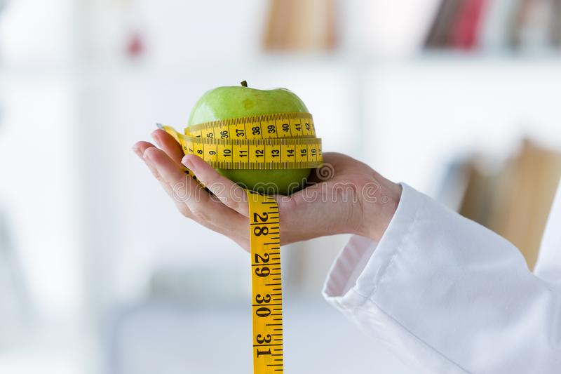 Mano femenina que sostiene una manzana verde envuelta en una cinta métrica fotografía de archivo