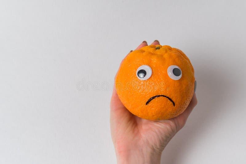 Mano femenina sosteniendo naranja triste Gracioso personaje de fruta naranja Sonrisa mandarina fotos de archivo libres de regalías