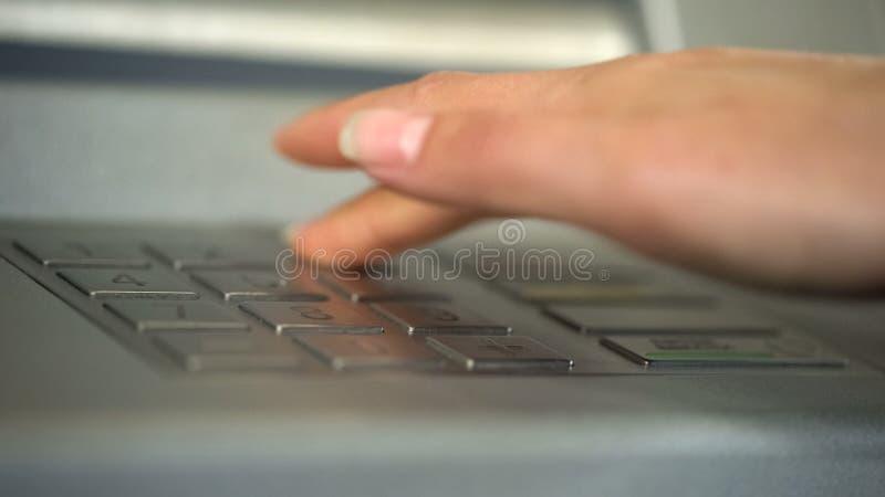 Mano femenina usando el cajero automático, insertando código personal único y presionando los botones foto de archivo libre de regalías