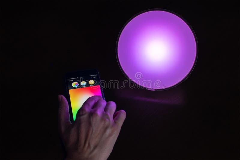 Mano femenina usando el iPhone de Apple para controlar una luz casera elegante de Philips Hue imágenes de archivo libres de regalías