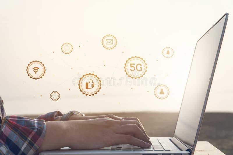 Mano femenina usando el ordenador portátil que comprueba medios sociales con tecnología del icono imagen de archivo