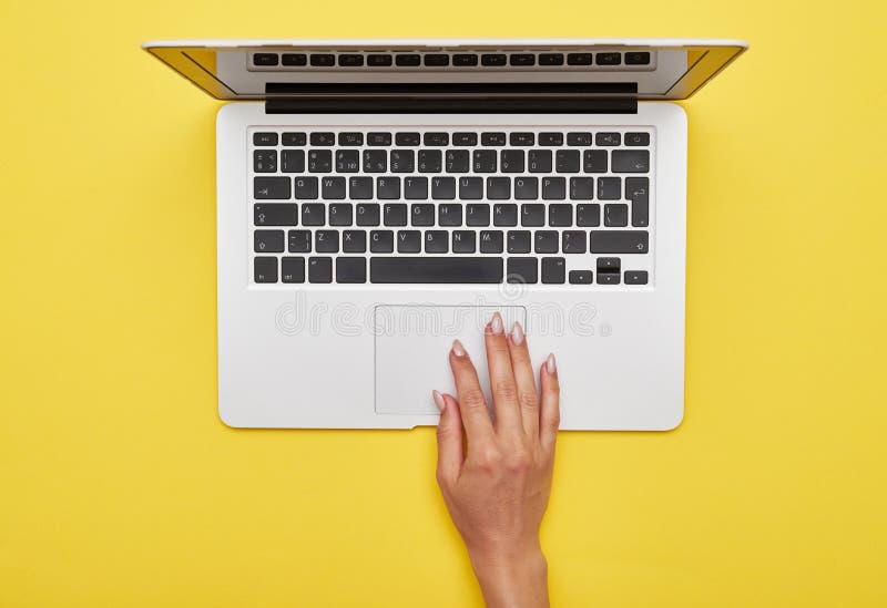 Mano femenina usando el panel táctil del ordenador portátil foto de archivo