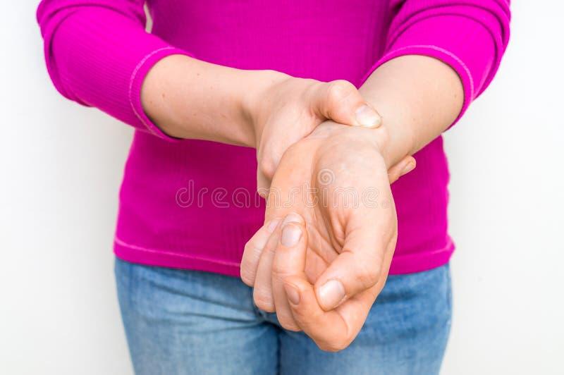 Mano femminile che controlla impulso di frequenza cardiaca sul polso immagine stock