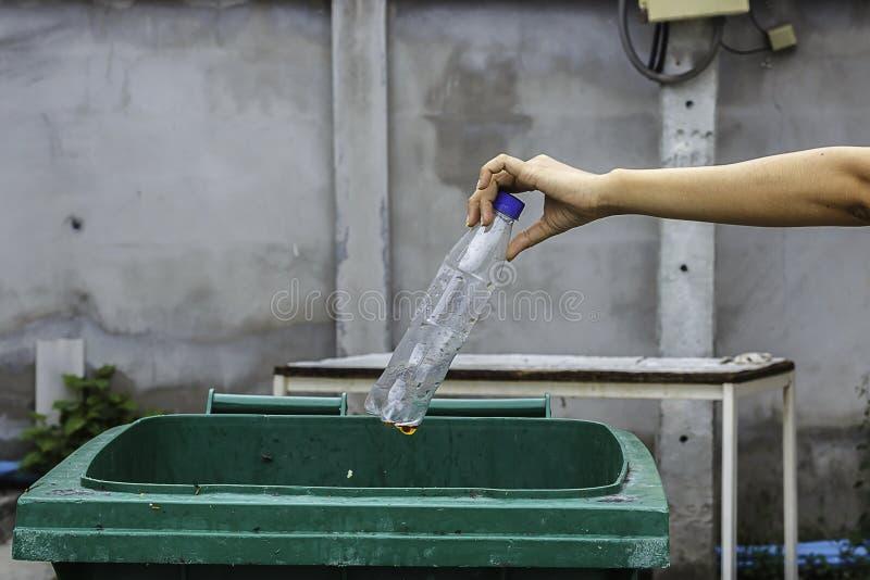Mano femminile che getta bottiglia di plastica vuota nei rifiuti immagini stock libere da diritti