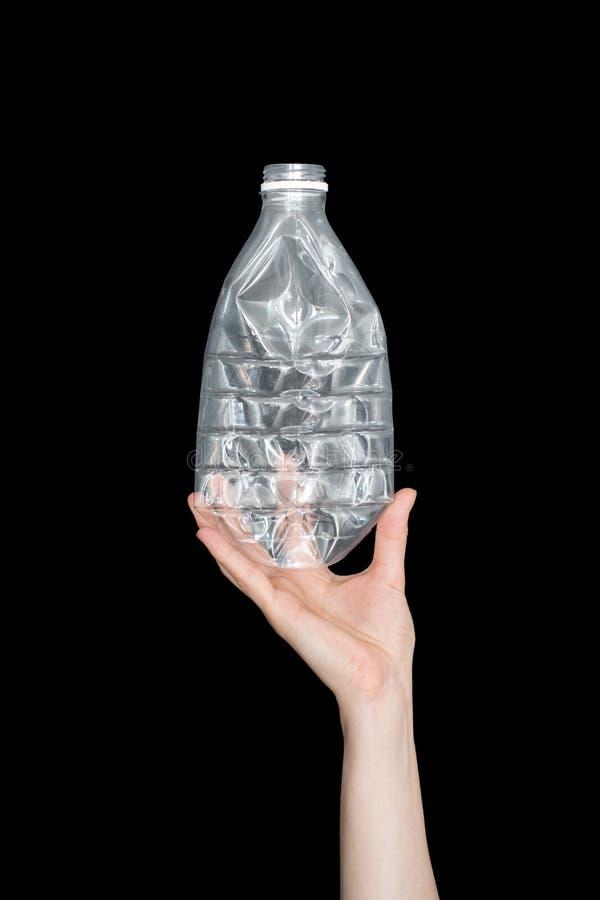 Mano femminile che giudica bottiglia di plastica schiacciata vuota isolata su fondo nero Spreco riciclabile Riciclando, riutilizz fotografie stock