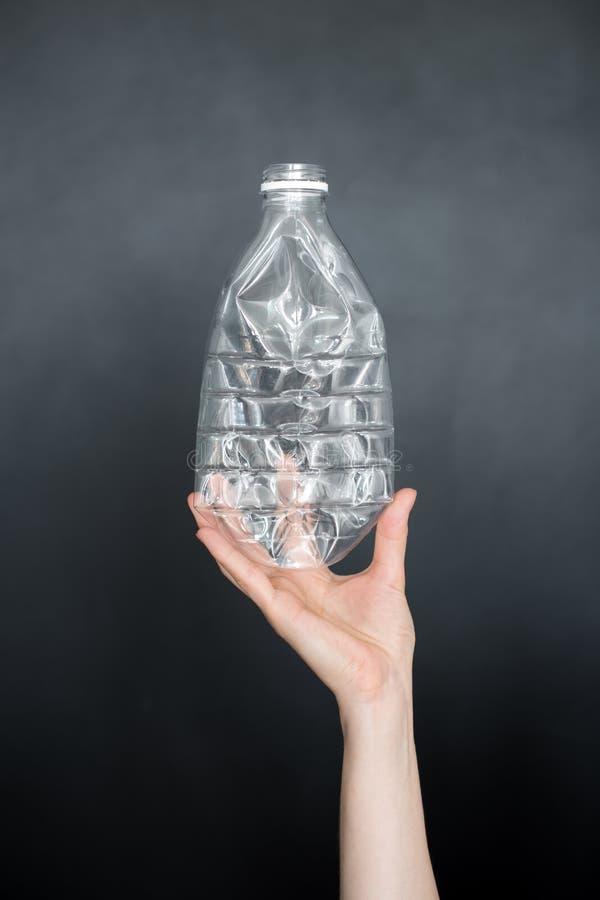 Mano femminile che giudica bottiglia di plastica schiacciata vuota isolata su fondo nero Spreco riciclabile Riciclando, riutilizz fotografia stock