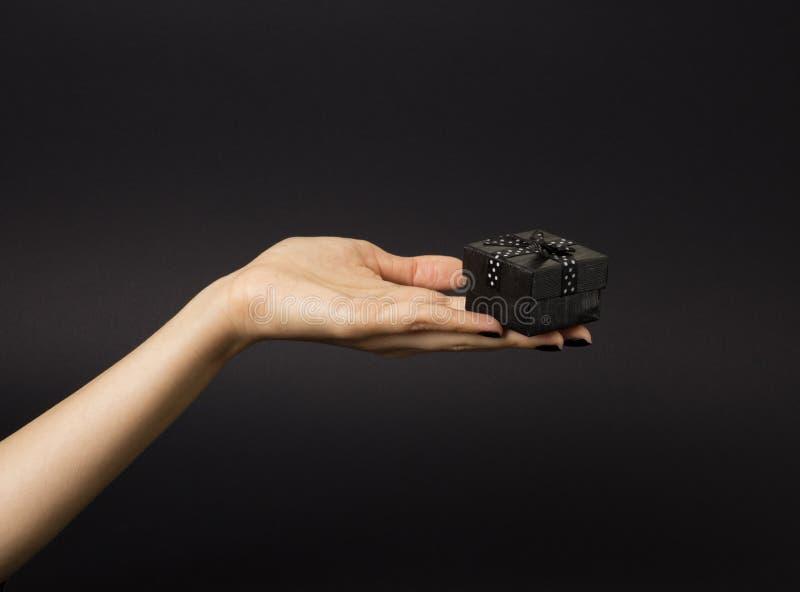 Mano femminile che giudica un contenitore di regalo nero decorato con il nastro nero con i pois bianchi su  immagini stock libere da diritti