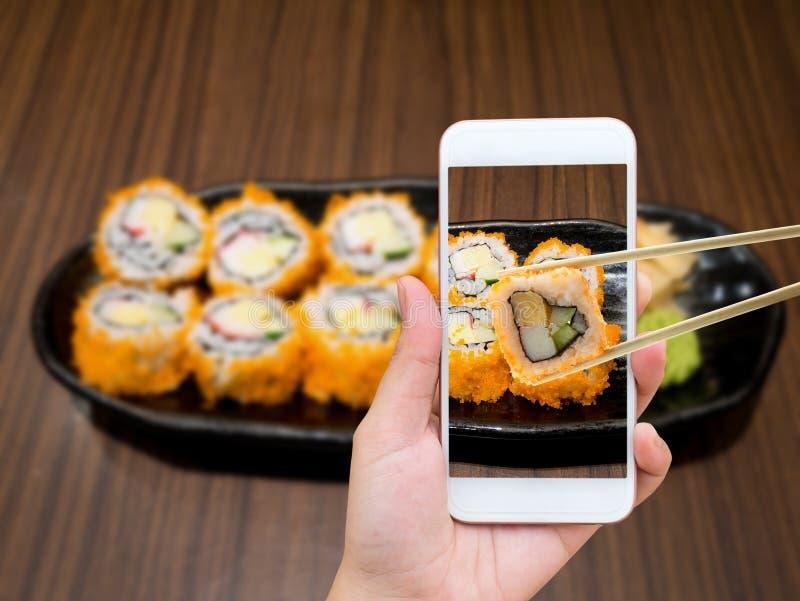 Mano femminile che prende foto dei sushi di maki con il telefono cellulare immagini stock libere da diritti