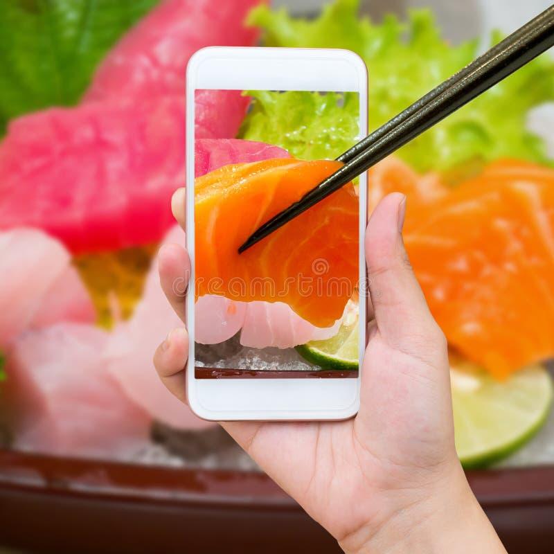 Mano femminile che prende foto dell'insieme dei sushi del sashimi immagini stock libere da diritti