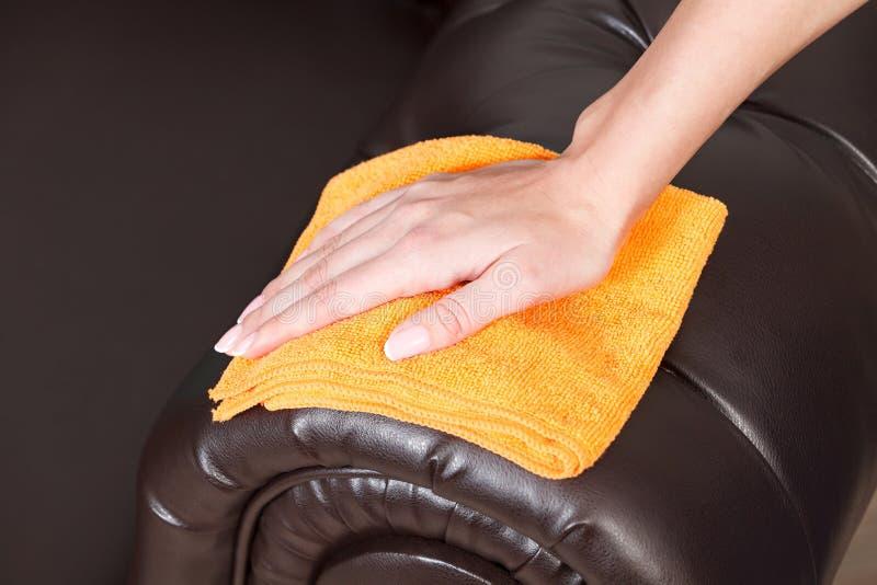 Mano femminile che pulisce lo strato o il sofà di cuoio marrone di Chester immagini stock libere da diritti