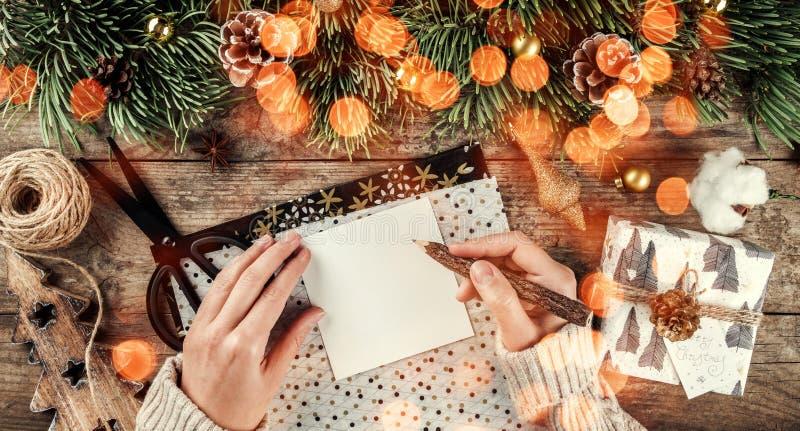 Mano femminile che scrive una lettera a Santa sul fondo di legno con i regali di Natale, rami dell'abete, decorazione dell'oro, p fotografia stock