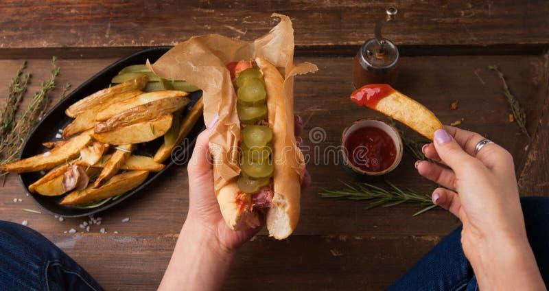 Mano femminile che tiene hot dog e le patate fritte americani tradizionali sul bordo di legno Vista superiore fotografie stock