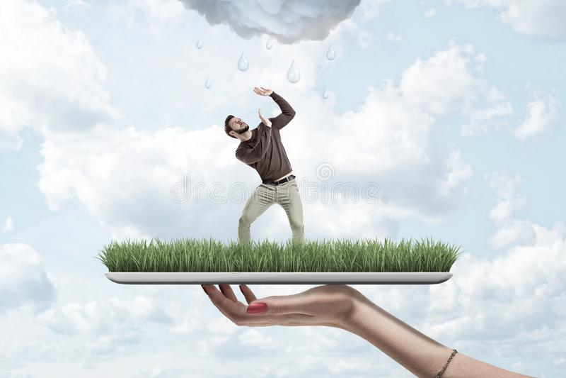 Mano femminile che tiene piccolo uomo in abbigliamento casual che si protegge dalla nuvola piovosa sul modello dell'erba verde co immagini stock