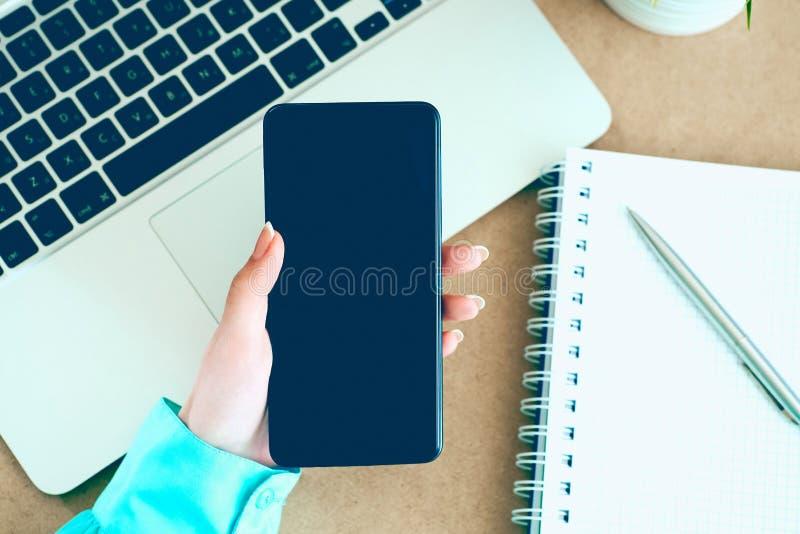 Mano femminile che tiene Smart Phone mobile nero con lo schermo in bianco sul fondo del blocco note e del computer portatile fotografia stock