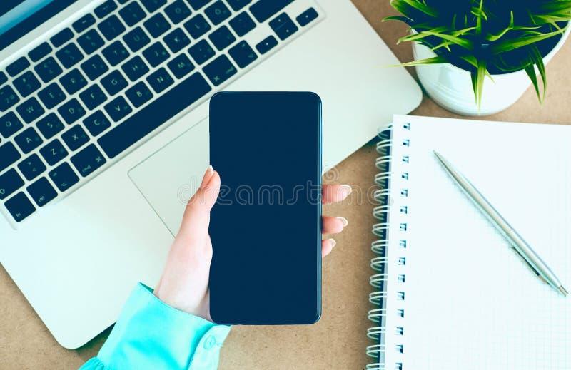 Mano femminile che tiene Smart Phone mobile nero con lo schermo in bianco sul fondo del blocco note e del computer portatile immagini stock libere da diritti