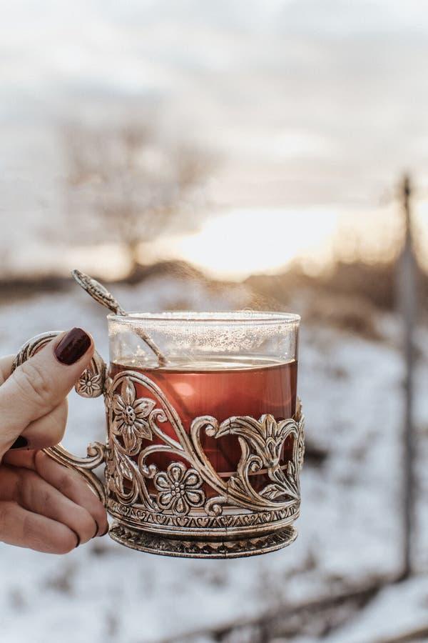 Mano femminile che tiene tazza d'annata con tè nero fotografia stock libera da diritti