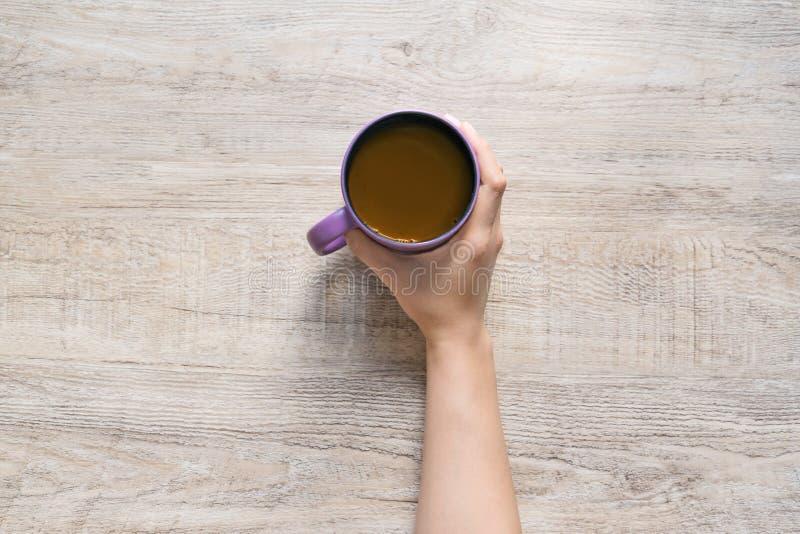 Mano femminile che tiene tazza di caffè sul fondo di legno di struttura fotografie stock libere da diritti