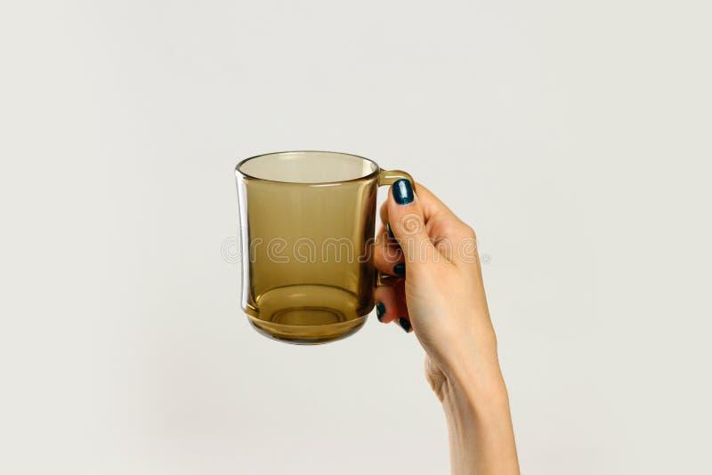 Mano femminile che tiene tazza di vetro vuota nera Isolato su fondo grigio immagini stock