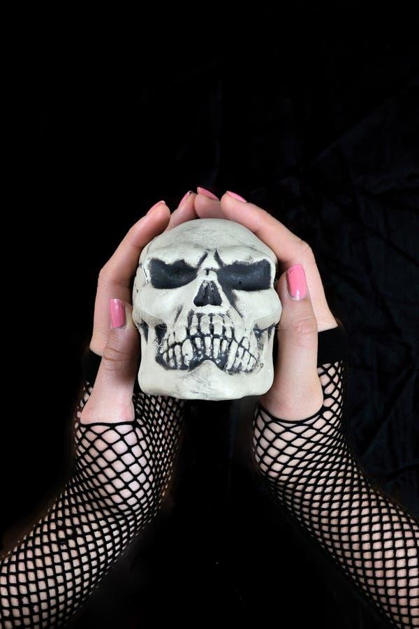 Mano femminile che tiene un cranio in sua mano fotografia stock
