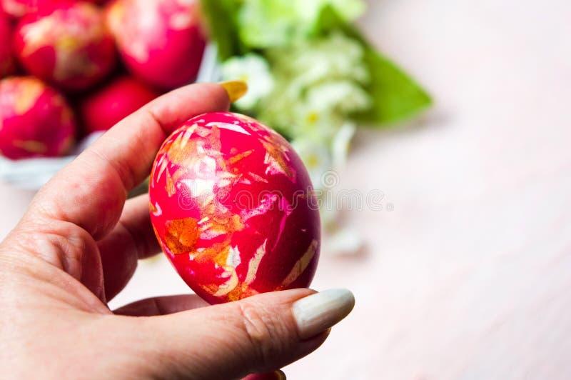Mano femminile che tiene un uovo di Pasqua fotografie stock libere da diritti