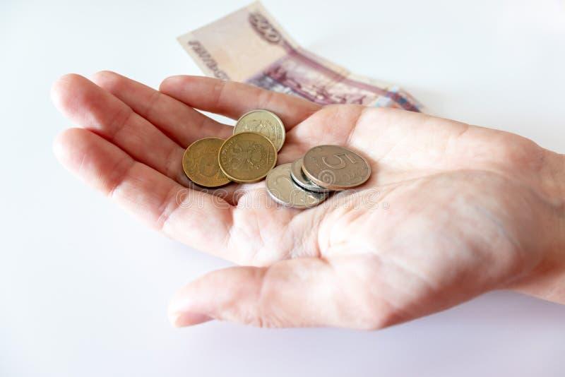 Mano femminile che tiene una moneta, le monete e le rubli russe sulla tavola fotografie stock