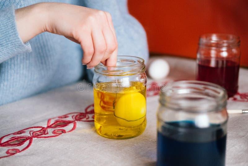 Mano femminile che tinge l'uovo di Pasqua su liquido giallo immagine stock