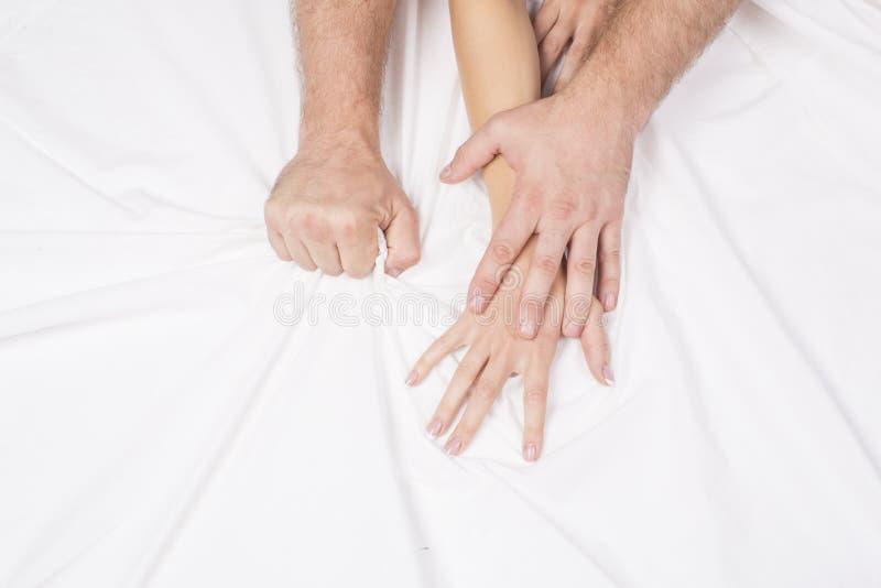 Mano femminile che tira gli strati bianchi nell'estasi, orgasmo Concetto di passione Momenti erotici Coppie del sesso bedroom immagini stock
