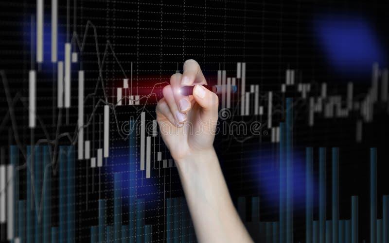 Mano femminile che traccia i grafici finanziari astratti su fondo scuro blu confuso Candele di grafico dei forex immagine stock