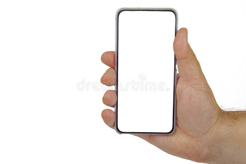Mano femminile con cellulare nero con schermo bianco su fondo isolato fotografia stock