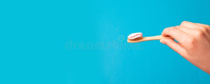 Mano femminile con dentifricio in pasta sulla spazzola contro fondo blu immagine stock libera da diritti