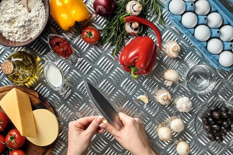 Mano femminile con il coltello sul tavolo da cucina del metallo, intorno agli ingredienti di bugia, alle verdure ed alle spezie p fotografia stock