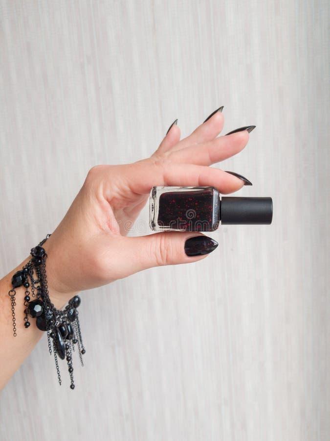 Mano femminile con il manicure e la bottiglia neri immagine stock