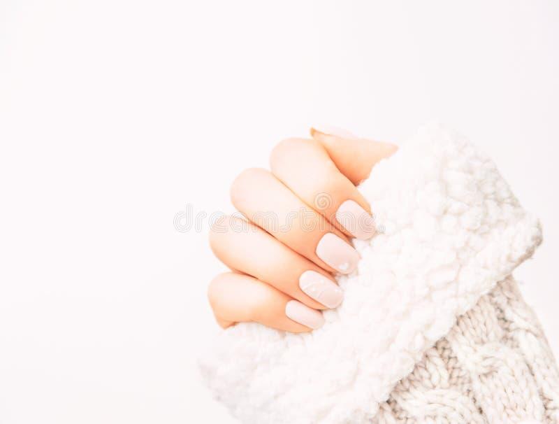 Mano femminile con il manicure professionale che dura in maglione della lana immagine stock