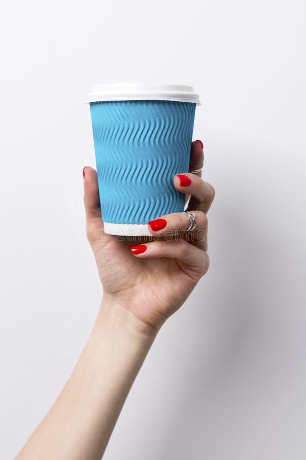 Mano femminile con il manicure rosso che tiene una tazza di carta del caff? su bianco fotografie stock