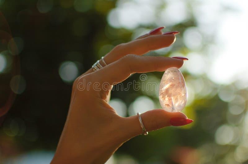 Mano femminile con l'uovo ametista trasparente di yoni del quarzo per vumfit, imbuilding o la meditazione Uovo di cristallo brill fotografia stock