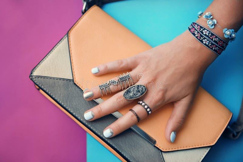 Mano femminile con la borsa di frizione e dei gioielli fotografia stock