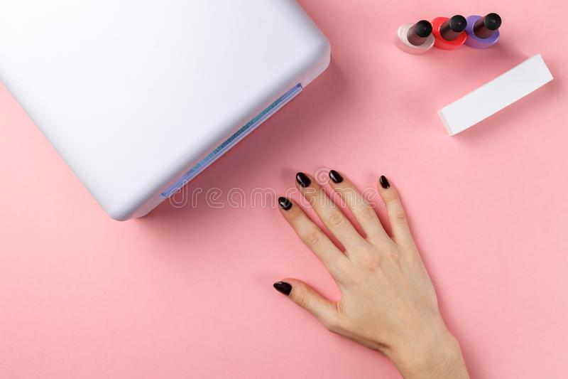 Mano femminile con la mano del manFemale con le unghie dipinte e la lampada UV immagini stock libere da diritti
