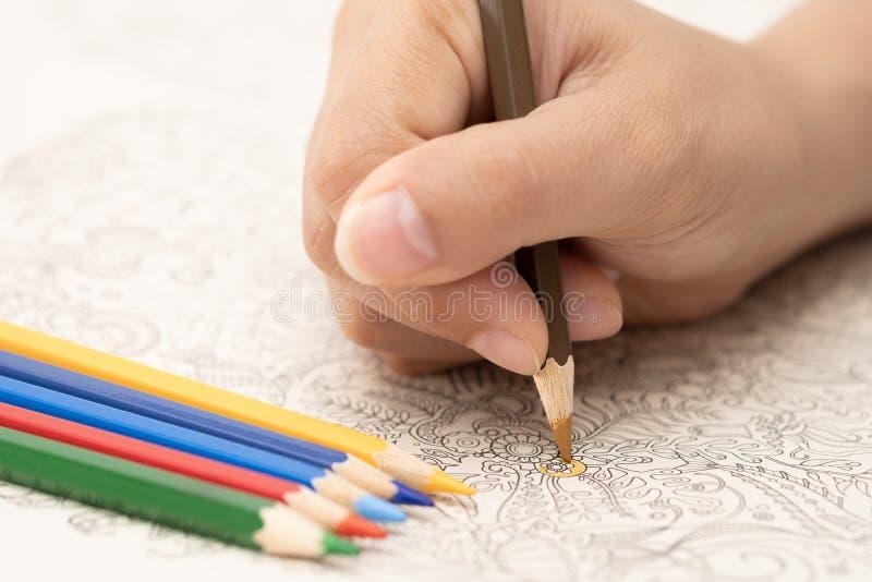 Mano femminile con la matita variopinta su fondo bianco fotografie stock libere da diritti