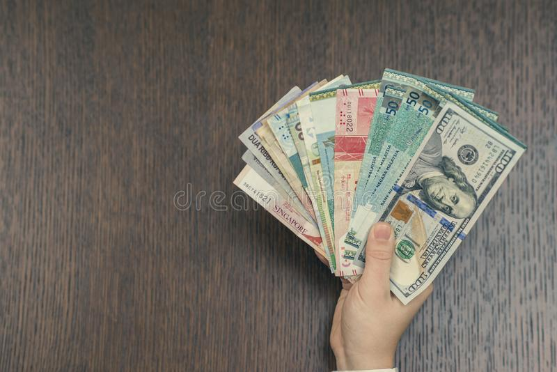 Mano femminile con soldi di Sud-est asiatico e della banconota in dollari dell'americano cento Valuta di Hong Kong, Indonesia, Ma immagini stock