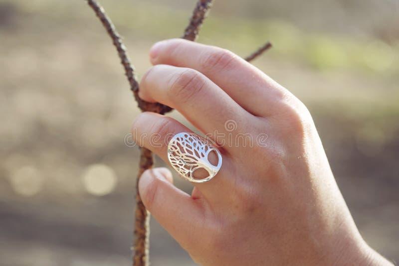 Mano femminile con un bell'anello d'argento immagini stock