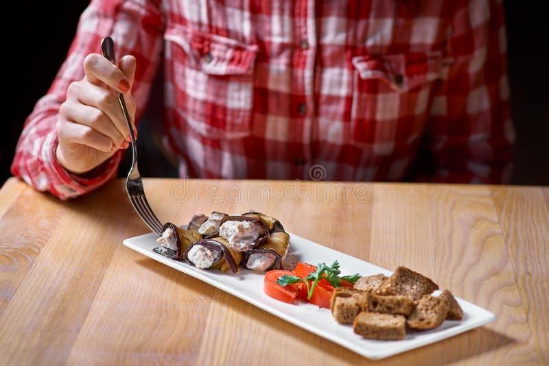 Mano femminile con una forcella, un piatto dei rotoli fritti della melanzana con le noci, aglio, briciole di pane Aperitivo fredd fotografie stock