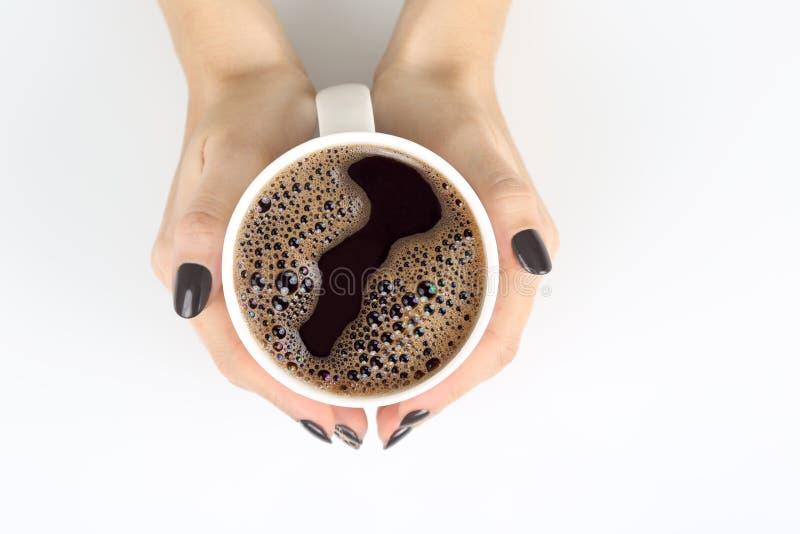Mano femminile con una tazza di caffè nero sul piano d'appoggio bianco fotografia stock
