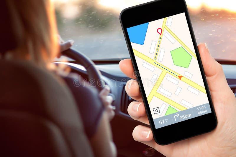 Mano femminile del driver che tiene un telefono con il navigatore dell'interfaccia sulla a immagini stock libere da diritti