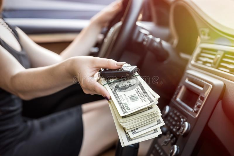 Mano femminile dentro le chiavi ed i dollari d'offerta dell'automobile fotografia stock