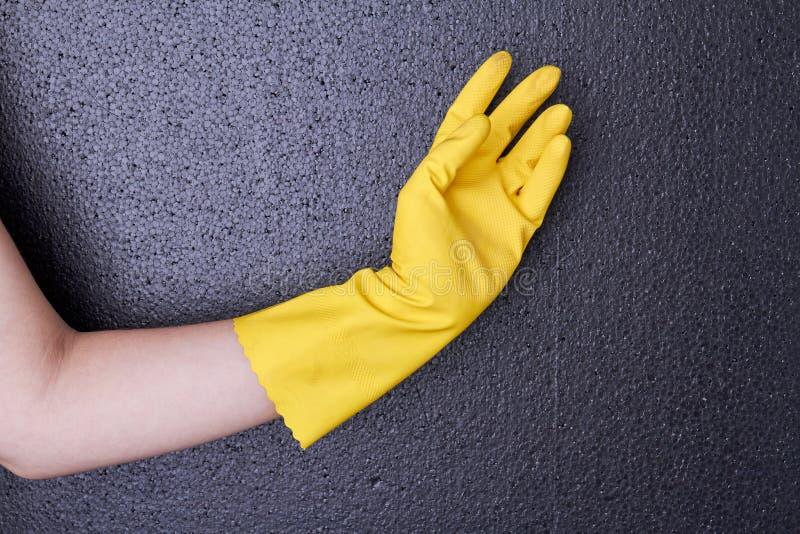 Mano femminile in guanto di gomma giallo immagine stock