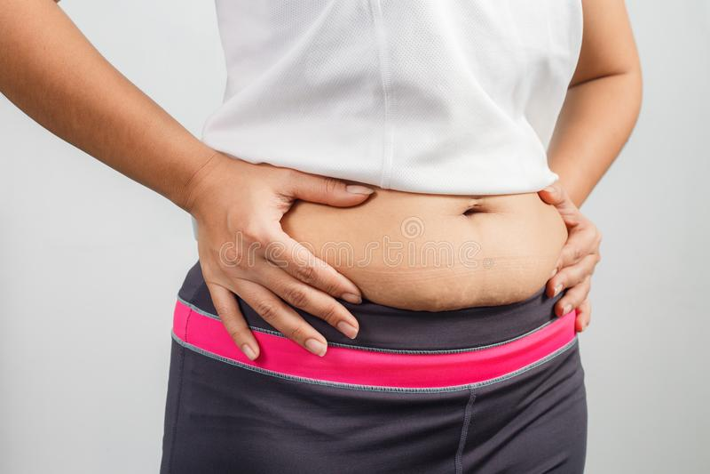 Mano gorda de la mujer que pellizca el vientre excesivo gordo imagen de archivo libre de regalías