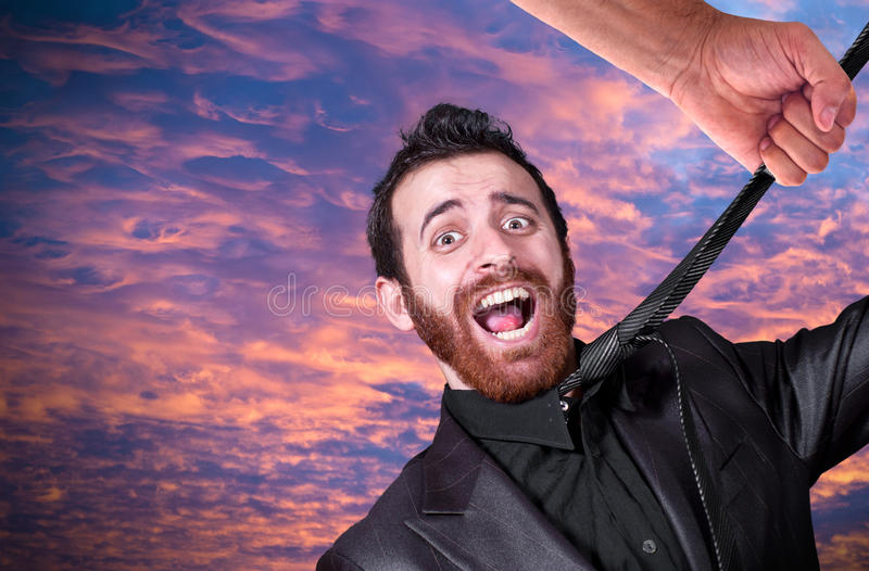 Mano grande que ase la corbata del hombre de negocios joven imágenes de archivo libres de regalías