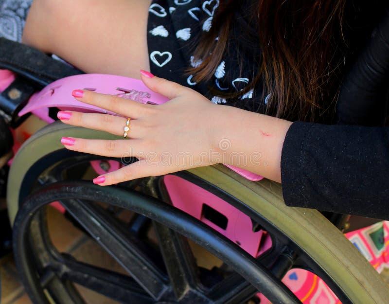 Mano graziosa dalla ragazza con l'inabilità facendo uso della sua sedia a rotelle rosa fotografia stock libera da diritti